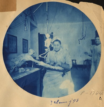 A woman sitting facing the camera in an operating room with a cadaver next to her. She is dissecting the hand while another woman stands nearby.