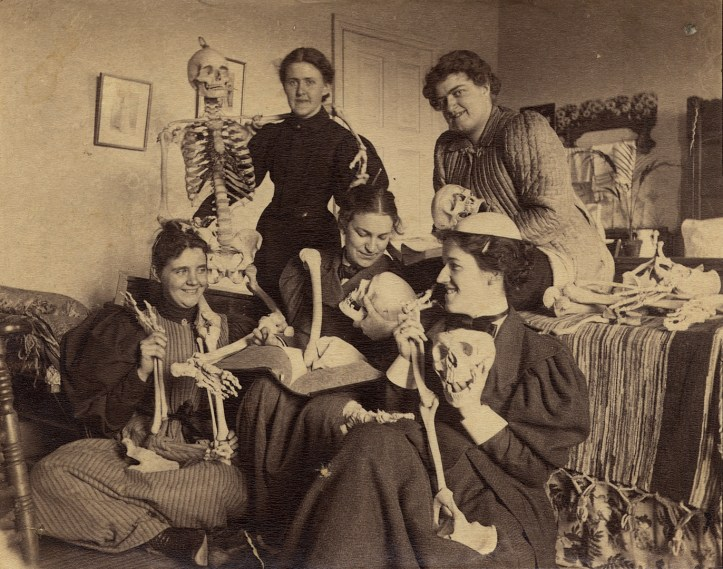 Five women, three seated and two standing behind them, joke with human bones while one appears to be studying a skull with a large textbook in her lap. One has a portion of a skull on her head and another has draped a skeleton arm across her shoulders.