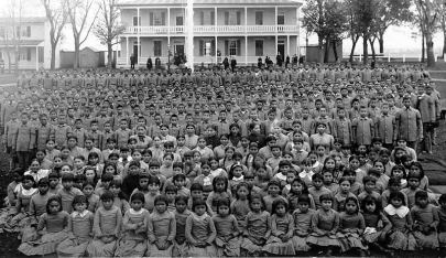 Hundreds of Native American children sit posed for a photo in uniforms.