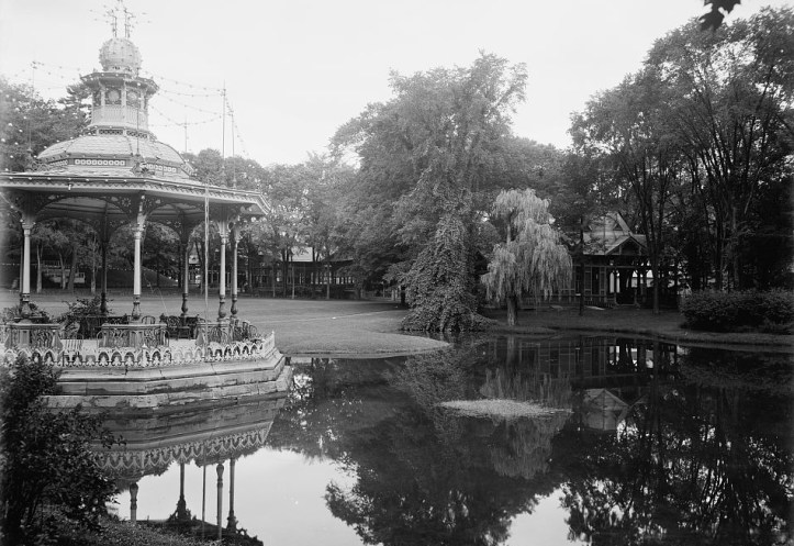 An ornate gazabo sits beside a smooth pond surrounded by short cut grass and tall trees.