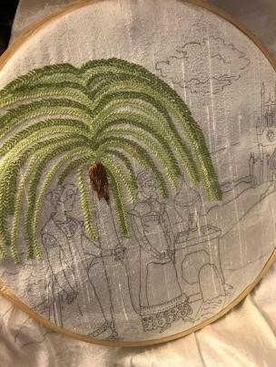 An in-progress work of embroidery showing a stitched flowing green tree and under it planned sketches for two people standing and looking down at a grave, with a church and clouds in the background.