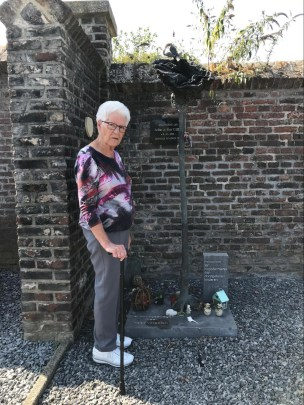 A standing woman with white hair holding a cane standing next to a small monument consisting of a flat concrete block with a tree sculpture and some small items, in the corner of a brick-walled graveled area.
