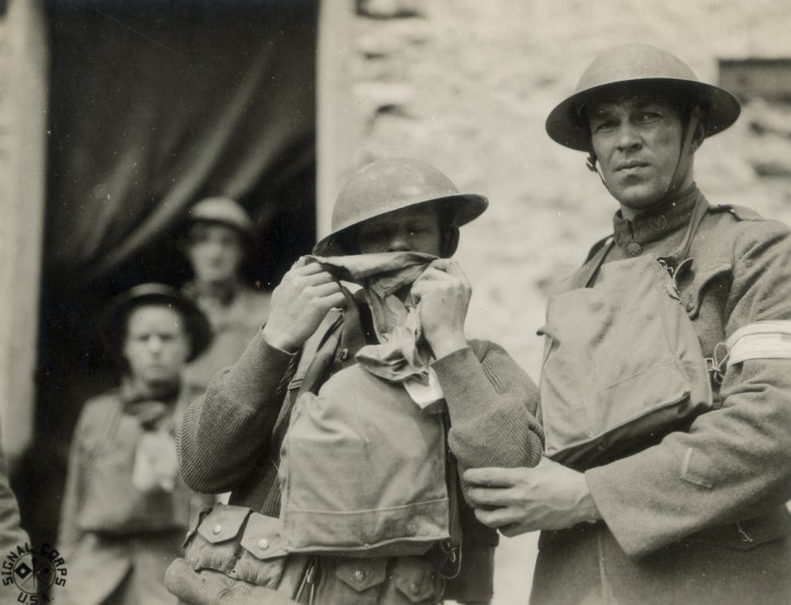 Soldiers standing in front of a stone wall. One man breathes into a canvas bag.