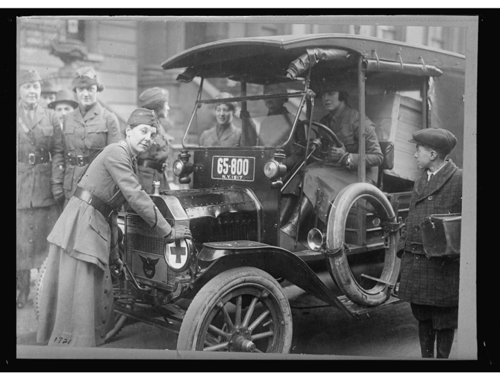 Captain A.B. Bayle is shown cranking the car, prior to making her rounds in New York. Her ambulance is surrounded by other women in service uniforms.