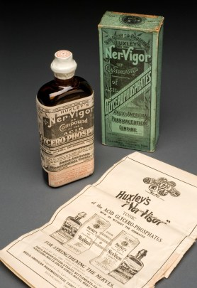 A small, old brown bottle alongside a green box and a leaflet describing the patent medicine.