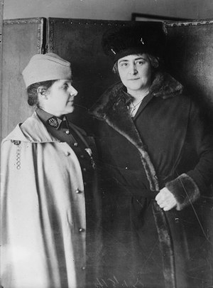 Two women in full-length coats and hats standing, one looking at the camera and the other at the other woman.
