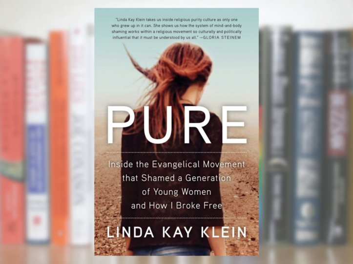 The cover of the book Pure, showing the title and a person with long hair facing away. The background is a blurry bookshelf.