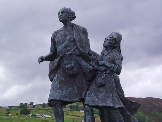Statue of a man wearing a kilt, with a girl child clutching at his hands.