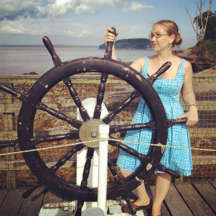 A woman (Briallen Hopper) in a blue sun dress stands at a recreation of a ship's wheel, looking into the distance.