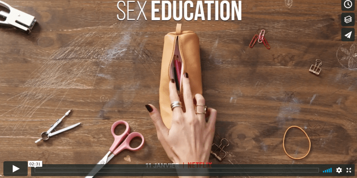 A hand opening a pencil case meant to look like a vulva.