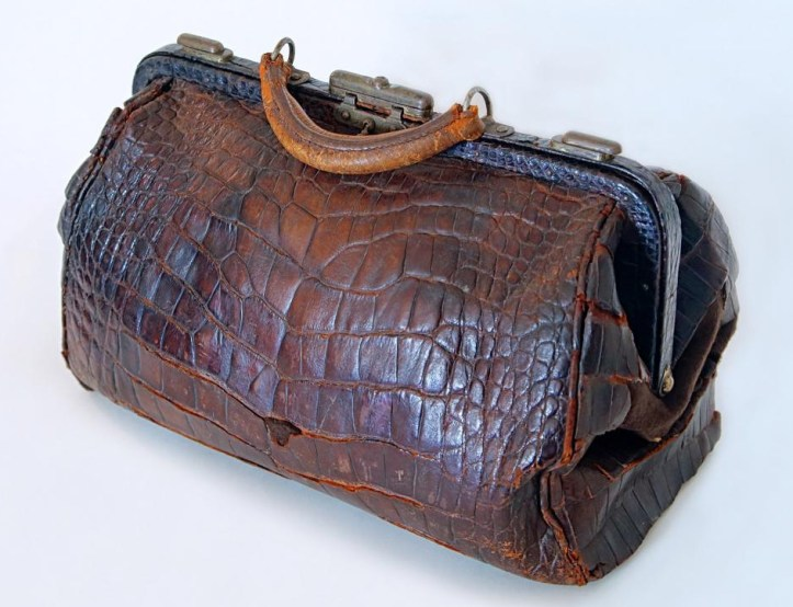 A large, dark reddish-brown alligator-skin purse with a metal clasp.