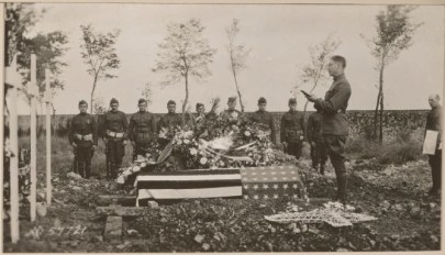 A flag-draped coffin with a line of men in uniforms standing at attention behind it and another reading over the coffin.