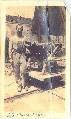 A man in a work uniform posing next to a WWI airplane engine.