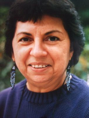 Headshot of a lighter-skinned woman with short black hair, beaded dangly earrings, and in a blue sweater.