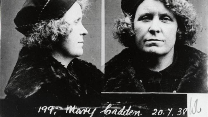 An old police mug shot of a woman wearing dark clothes and a hat.