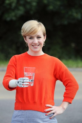 A white woman in an orange sweatshirt with a bionic arm holds up a glass of water with said arm.