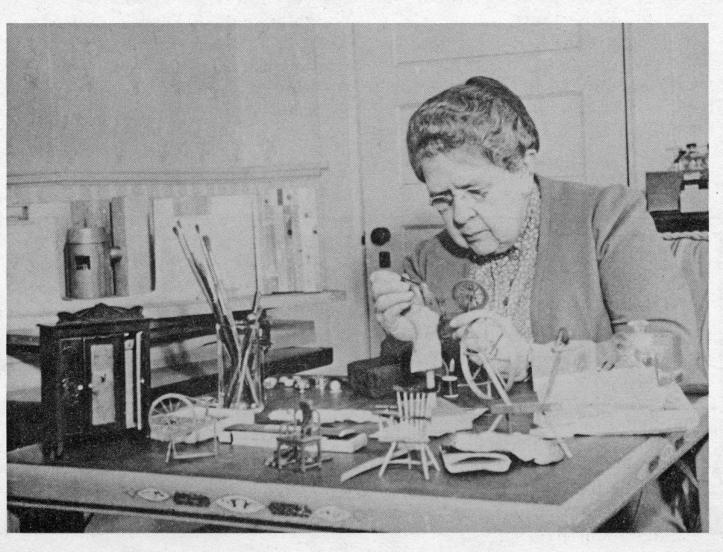 White woman with graying hair sits at a desk on which the components of a future diorama - a tiny doll sized chair, a doll she is building, and other iteams, are strewn across the desk