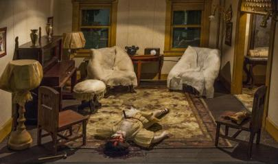diorama showing a girl laying on the floor with a knife sticking out of her belly. two arm chairs in the background corners of the room, some other furniture.