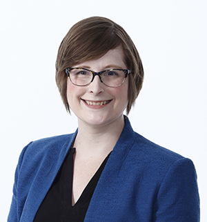 Emily Johnson, white woman wearing a blue blazer and black top, with short cropped hair and glasses