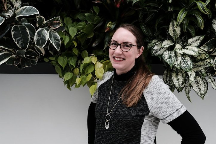 Sarah Handley-Cousins poses in front of a living wall, with lots of green leafys behind her