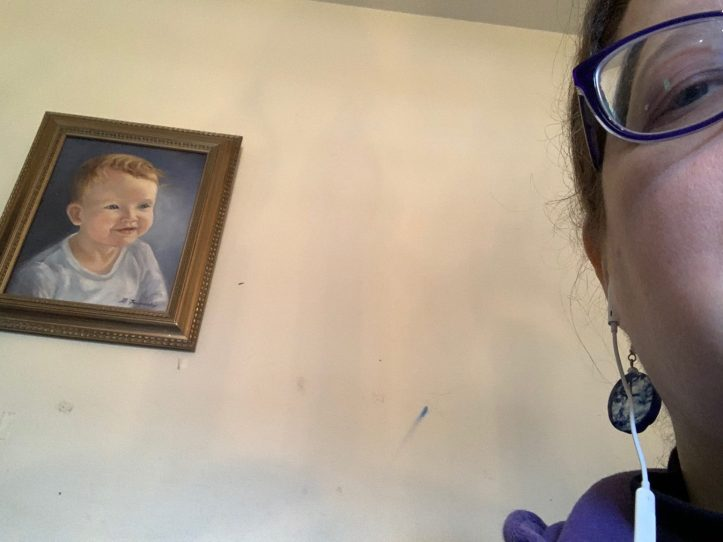 In the rightmost foreground is part of a woman's face, with her glasses and one earring showing; to the left of the photo is a painting of a baby hanging on a wall