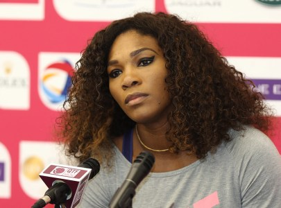 Serenca Williams sits in front of several microphones; the photo is from her shoulders up, she is wearing a gray top and gold ncklace, and her hair is loose and curly. She has a look of thoughtful incredulity on her face, or maybe sadness.