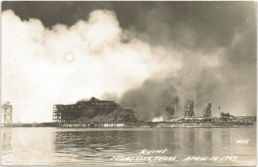 view from across a body of water, a thick white smoke cloud dominates to top half of the photo, obscuring what appear to be the burned-out buildings of the oil refinery.