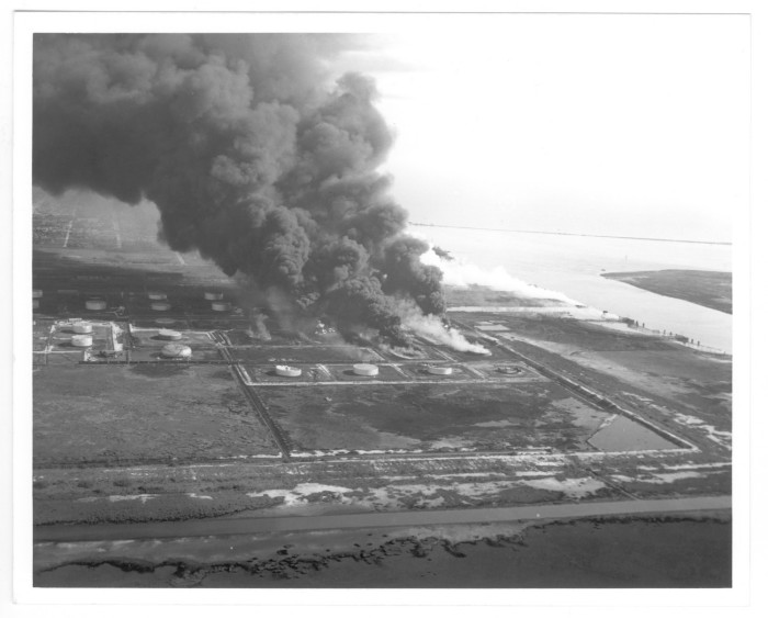 Aerial view of refineries and storage tanks, with plumes of black smoke rising from them