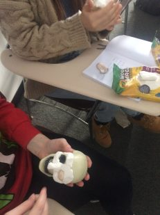 two young white people sit side by side owrking with crayola modeling clay to cover small plastic skulls in the clays in a mock up of human facial features