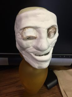 A plastic skull fully covered in modeling clay to resemble human features (lips, eyelids, a nose)
