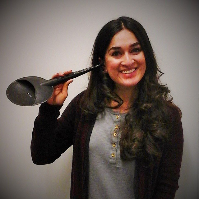 Jaipreet Virdi, a woman with long dark hair, stands holding an ear trumpet to her right ear.