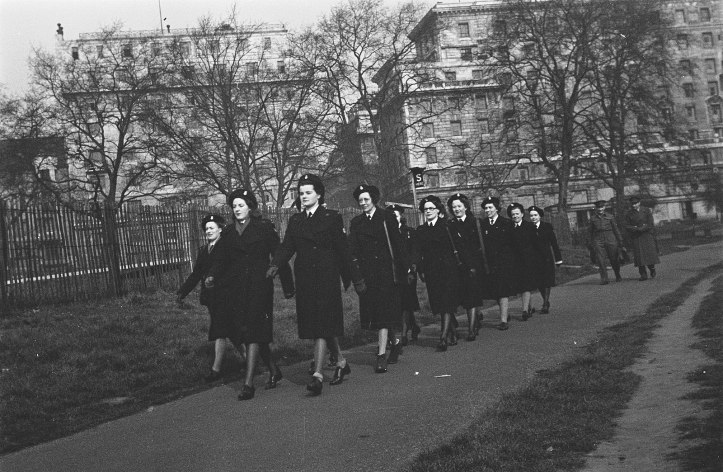 A black and white photo of a group of women marching along a road two-by-two. They all wear black uniforms and hats.