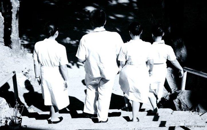 Four people in white nurse uniforms walking down steps