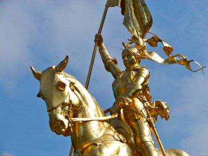 Joan of Arc is gilded in gold and rides on a horse holding a French flag aloft