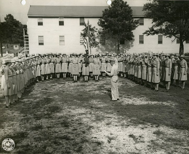 A group of women in army uniforms stand in a semi circle in front of a white building