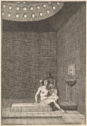 A woman sits topless in the corner of a room, overseen by another person