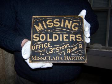 """A dark blue sign with the text """"Missing Soldiers Office, 3 rd Story, Room 9, Miss. Clara Barton."""""""