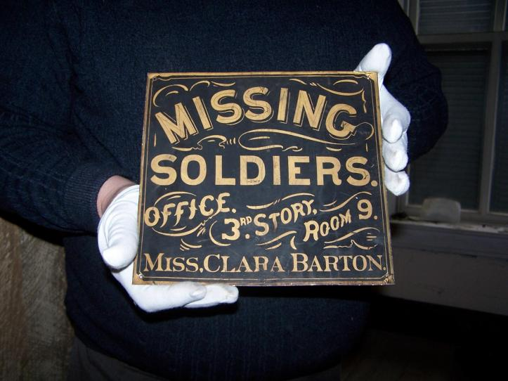 "A dark blue sign with the text ""Missing Soldiers Office, 3 rd Story, Room 9, Miss. Clara Barton."""