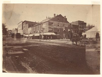A sepia tone photograph of a muddy street with brick buildings that are three or four stories tall on one side. The horse drawn ambulance at the lower right corner date the photograph.