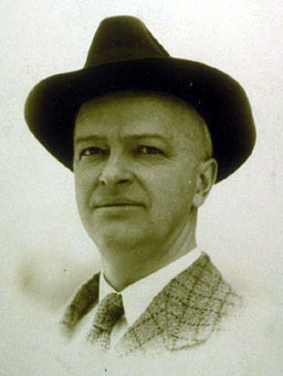 A black and white photo of a white man in a black hat.