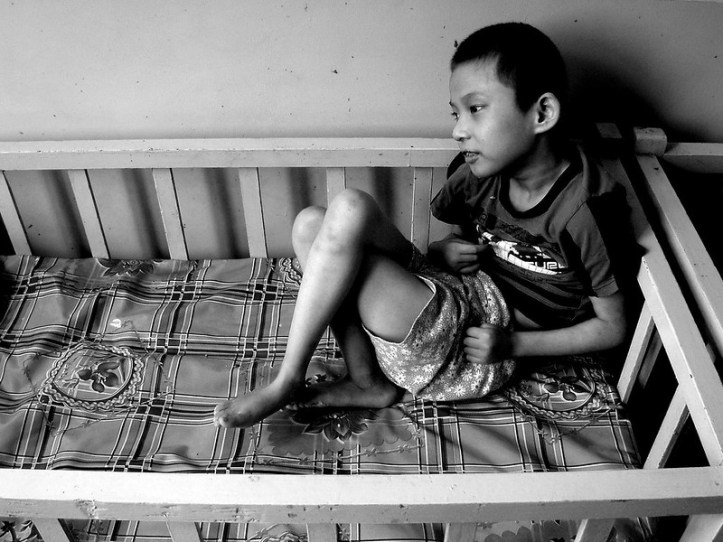 A young boy, about eight years old, sits in a crib.