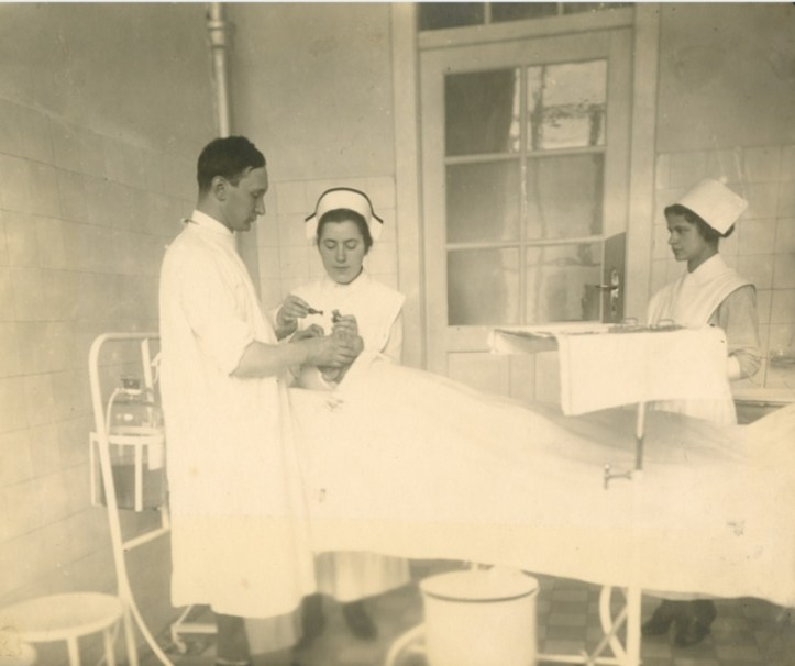 A doctor and nurse work on a patient's eyes as another nurse watches.