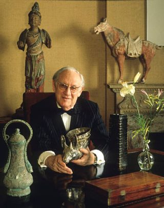 An elderly white man sits in a chair surrounded by collectible art and artifacts.