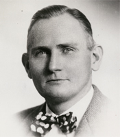 A black and white photo of a white man with short cropped hair, wearing a bowtie.