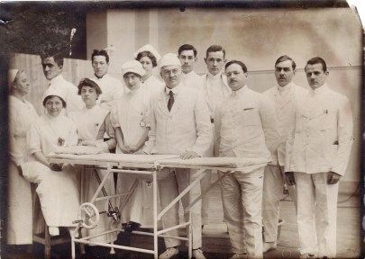 A group of white men and women pose in front of a narrow operating table. They're all dressed in white