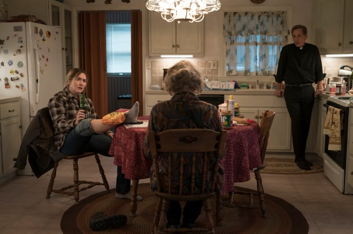 Characters from Mare of Easttown congregate in a kitchen. Kate Winslet holds a beer and looks surprised.