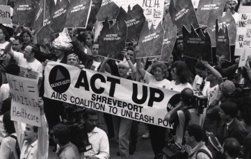 "Demonstrators hold a sign reading ""ACT UP Shreveport."""