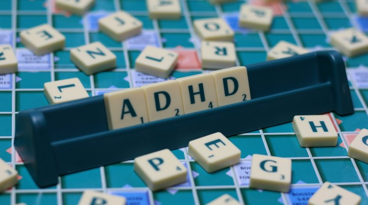 """A scrabble board with tiles spelling """"ADHD""""."""