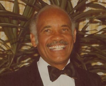 A Black man in a tuxedo grins.