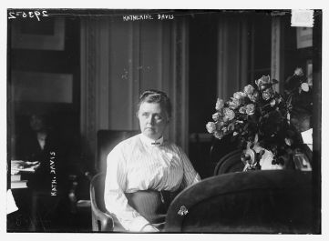 Katharine Bement Davis sits on a chair next to a vase of white flowers. She is wearing a white blouse tucked into a dark skirt.